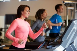 Woman and two young adults running on treadmills at a gym